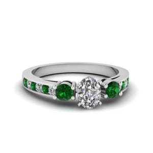 Oval Shaped Channel Three Stone Diamond Ring With Emerald In 18K White Gold